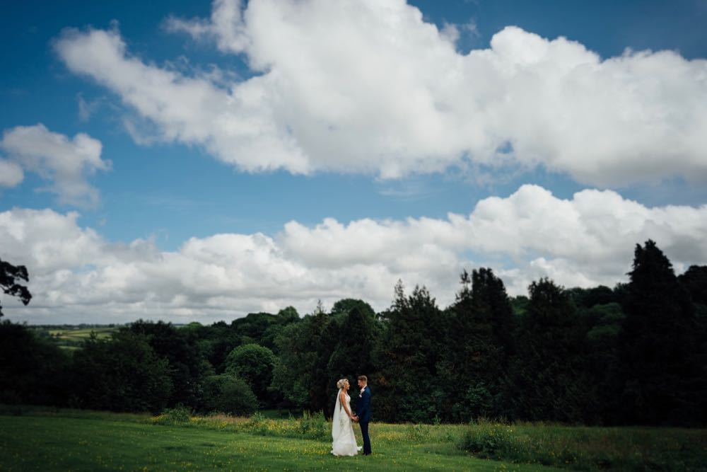 A shot of the couple with the Cornish landscape in the background. The couple are tiny compares to the background. There is a line of fir trees ion the horizon and the sky is blue with some clouds
