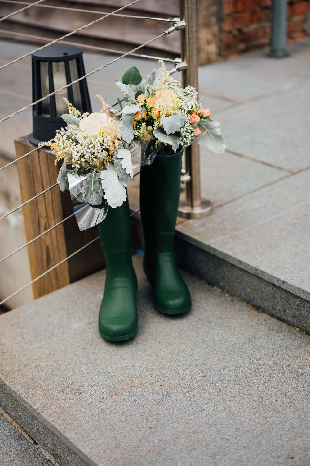 A decor detail shot of some flowers poking  out of a green welly