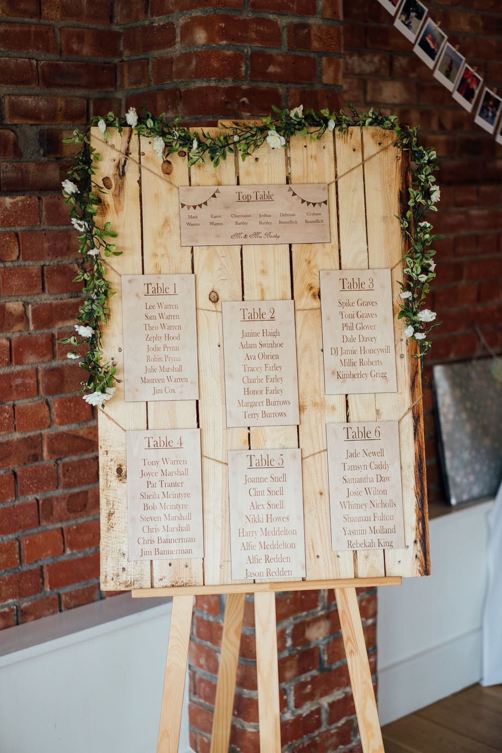 A decor detail shot of a table plan. With cards for each table. Teh plan is on our easel and there are flowers decorating the edge of the frame