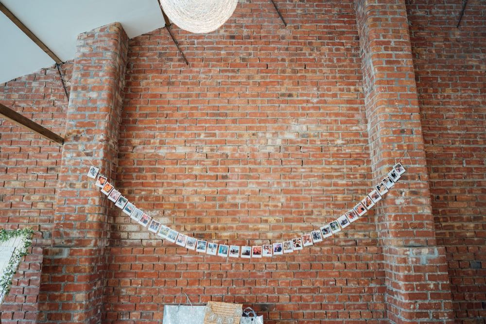 An image of the red brick wall on the inside of the red brick barn. There is a string of bunting on the wall. The bunting is made up of photos