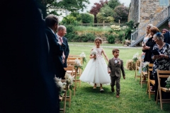 "A flower girl and page boy walking down the ""aisle\"" between 2 rows of chairs on the lawn"