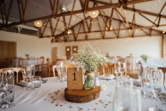 A shot of the inside of the Red Brick Barn set up for the wedding breakfast, There are round tables with white cloths. The centrepieces are log slices with jars of gyp