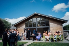 The front of the Green Room barn with guests sitting on tables outside