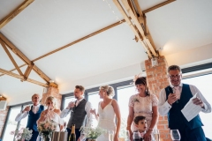 A picture taken in the Red Brick Barn. The picture is of the guests on the top table. Teh top table is set up in front of the windows. The guests are standing for a toast