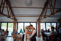 A picture taken in the Red Brick Barn. The shot is of the first dance. The couple are shown with the large window s in the background.
