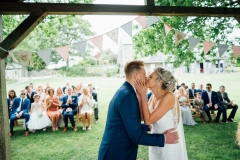 """You may kiss the bride\"" moment. The shot is taken from the back of the arbour with the couple in the foreground. It is taken from the waist up. The groom is  on the left and the bride is on the right. The groom wears  dark grey suit and the bride wears a white sleeveless dress. She has blond hair work up."