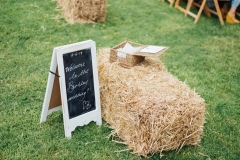 "A decor detail shot showing a straw bale on the lawn and a hand written a-fram chalk board. Th e sign reads "" Welcome to the Bartley wedding\"""
