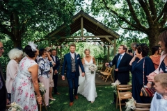 A full length shot of the couple walking away from the Oak Arbour after their ceremony. The couple are shown in full length with the arbour in the background. The groom is on the left and the bride is on the right. The groom wears a grey suit. The bride wears a full length, fitted, sleeveless , white dress and has a bouquet in her left hand