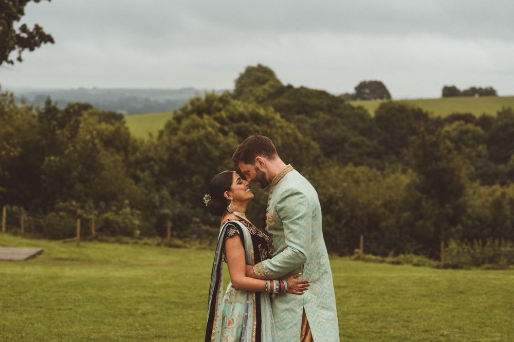 Couple in Indian wedding dress in front of the view in front of the Red Brick Barn