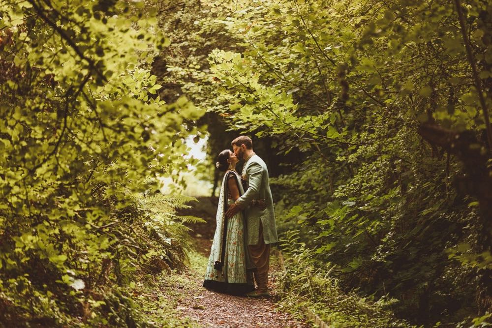 Couple in Indian wedding dress on the woodland walk. They are surrounded by green trees.
