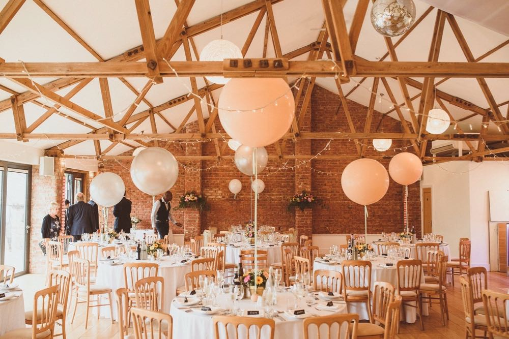 The Red Brick Barn all set up for a wedding reception with round tables and white linen. There is a larege white spherical abllonn in the centre of each table.