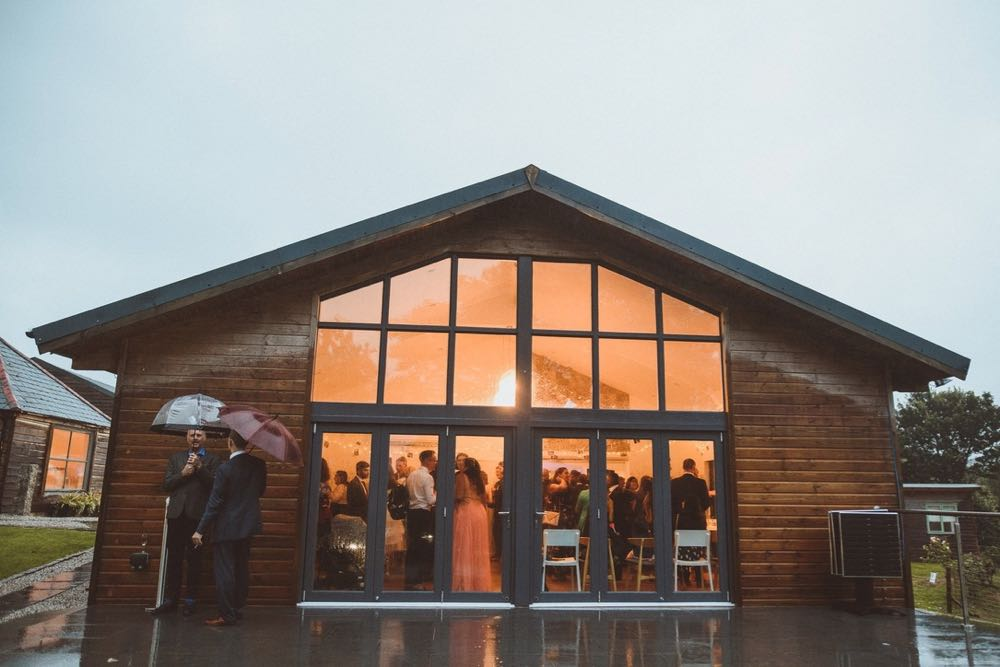 The Green Room Bar. The picture is taken from outside at dusk. The full length glass windows are lit up and you can see guests relaxing inside