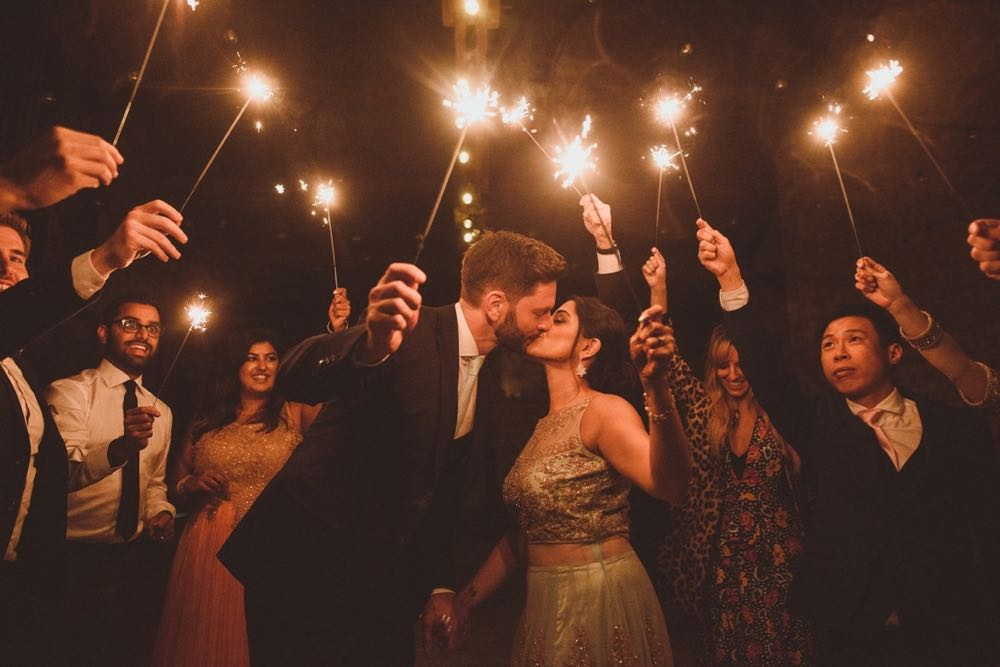 A sparkler exit. The couple kiss while holding up sparklers. They are surrounded by guests also with sparklers