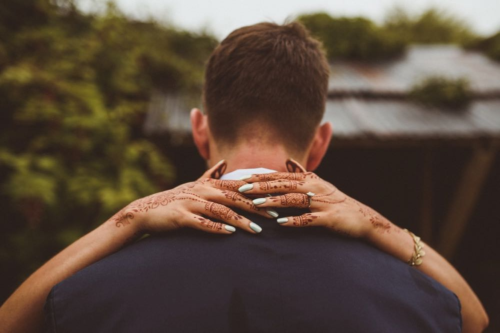 This omage is of the back of the grooms head and shoulders. He is wearing a blue suit jacket and has short mid-brown hair. The bride's hands are around his neck and they are decorated with henna.