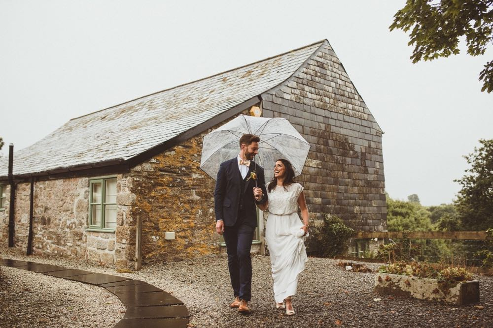 A bride and groom are walking in front of a granite stoen barn. The bride is on the right. They are holding hands and looking at each other and are under an umbrella.. The bride is wearing a long, white sleeveless dress and has her hair loose. The groom is wearing a dark, suit, white shirt and brown brogues. They are walking towards the camera.