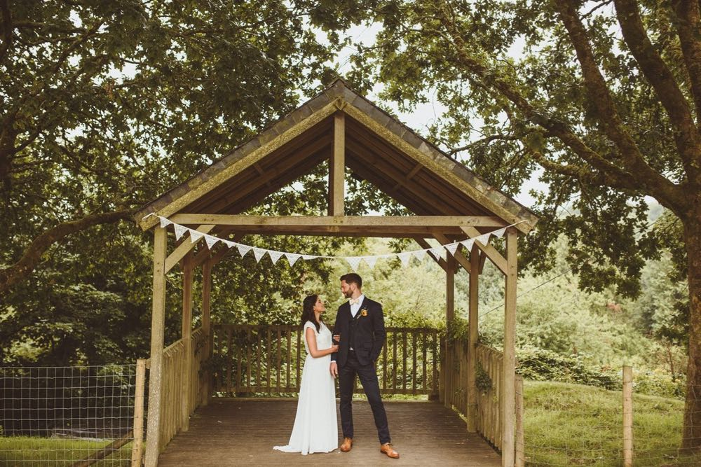 A bride and groom stand under the Oak Arbour. The bride is on the left. They are holding hands and looking at each other. The bride is wearing a long, white sleeveless dress and has her hair loose. The groom is wearing a dark, suit, white shirt and brown brogues.