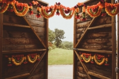 A shot through the door of the Really Rustic Barn showing part of the view beyond. Ther are orange floral garlands on the door.