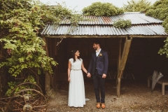 A bride and groom stand in front of an open fronted shed. The bride is on the left. They are holding hands and looking at each other. The bride is wearing a long, white sleeveless dress and has her hair loose. The groom is wearing a dark, suit, white shirt and brown brogues.