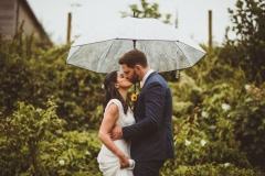 A bride and groom kiss under an umbrella in front of lots of greenery. The bride is on the left.  The bride is wearing a long, white sleeveless dress and has her hair loose. The groom is wearing a dark, suit, white shirt and brown brogues.