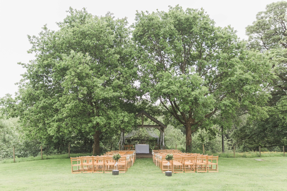 The Oak Arbour in May with each tree in full leaf. A full length shot showing the arbour set between 2 large oak tress. Wooden chairs are set out in the grass in frot of the arbour and the trees are in full leaf.