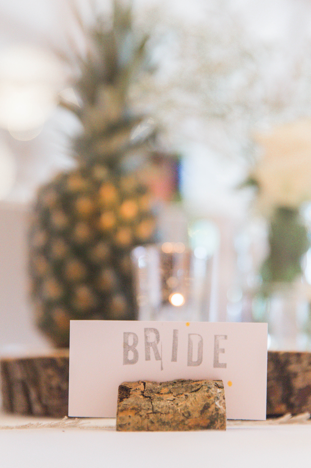 """A close up shot showing the detail of the table decor. There is a large  pineapple in the background sitting on a log slice. The table linen is white and there is a table place name set in a wooden holder. The sign says \""""BRIDE\""""."""