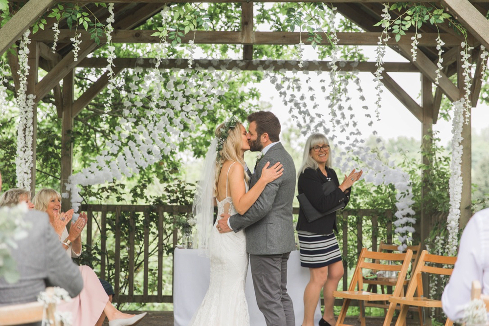 """This is a picture of the bride and groom under the arbour  after the registrar has said \""""you may kiss the bride\"""". The couple are facing each other and kissing. The bride is on the left. She is  wearing a white, fitted, sleeveless dress with shoestring straps. She has blond hair that she is wearing loose. She is wearing  a flower garland and a veil. The groom is wearing a light grey suit. He has dark hair and a beard"""