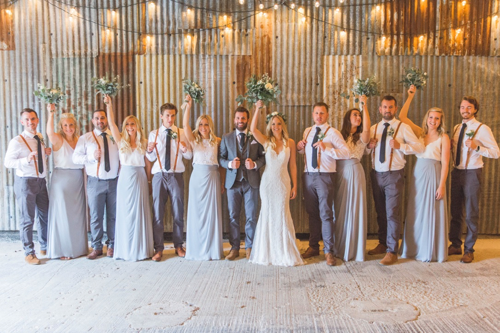 This is a picture of the bridal party in the really Rustic Barn. They ar standing in front of the corrugated iron clad wall. The group is made up of the bride and groom, 5 bridesmaids and 6 groomsmen. The bridesmaids are wearing long grey skirts and white blouses. The groomsmen are wagon brown loafers, grey trousers, blue ties, white shirts and red braces. Each bridesmaid and the bride is raising her bouquet into the air. The photo shows them in full length and there is festoon lighting above them.