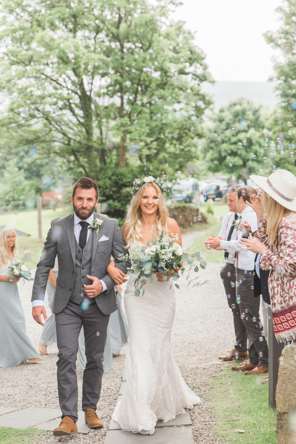 This is a picture of the bride and groom walking towards the Green Room after the cermeonyarbour. The bride is on the right. She is  wearing a white, fitted, sleeveless dress with shoestring straps. She has blond hair that she is wearing loose. She is wearing  a flower garland and a veil. The groom is wearing a light grey suit. You can see guests standing beside them. They are linking arms and walking towards the camera. the shot is from the knees up. There are trees and stone barns in the background.