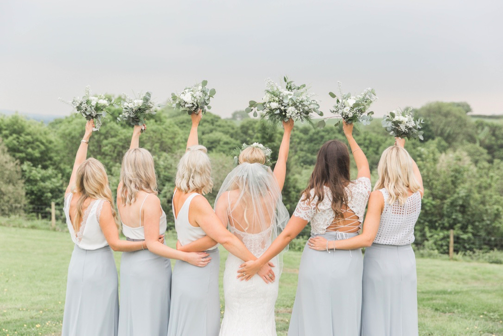 This is a picture of the bride and bridesmaids standing on the lawn in front of the Red Brick barn. They are standing in front of the camera with their back to it and you can see a view of a green landscape in the background. The bride is in the middle with 2 bridesmaids on either side. The bridesmaids are wearing long grey skirts and white blouses.  Each bridesmaid and the bride is raising her bouquet into the air. The photo shows them from the knees up,