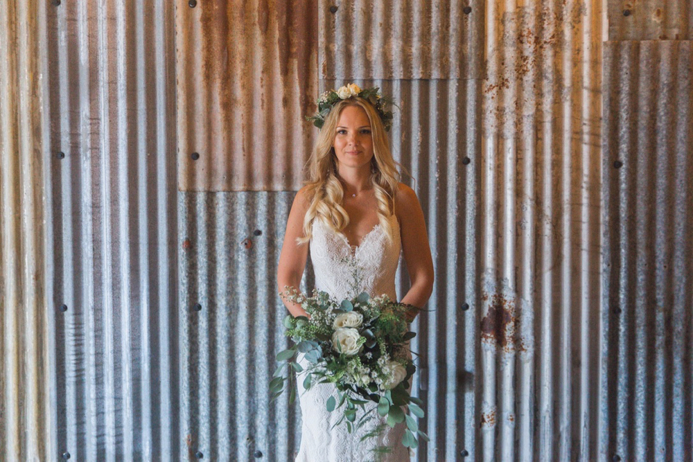 This is a picture of the bride in the really Rustic Barn. She is standing in front of the corrugated iron clad wall.  The photo shows her  from the knees up. She is  wearing a white, fitted, sleeveless dress with shoestring straps. She has blond hair that she is wearing loose. She is wearing  a flower garland and a veil and is holding a bouquet.