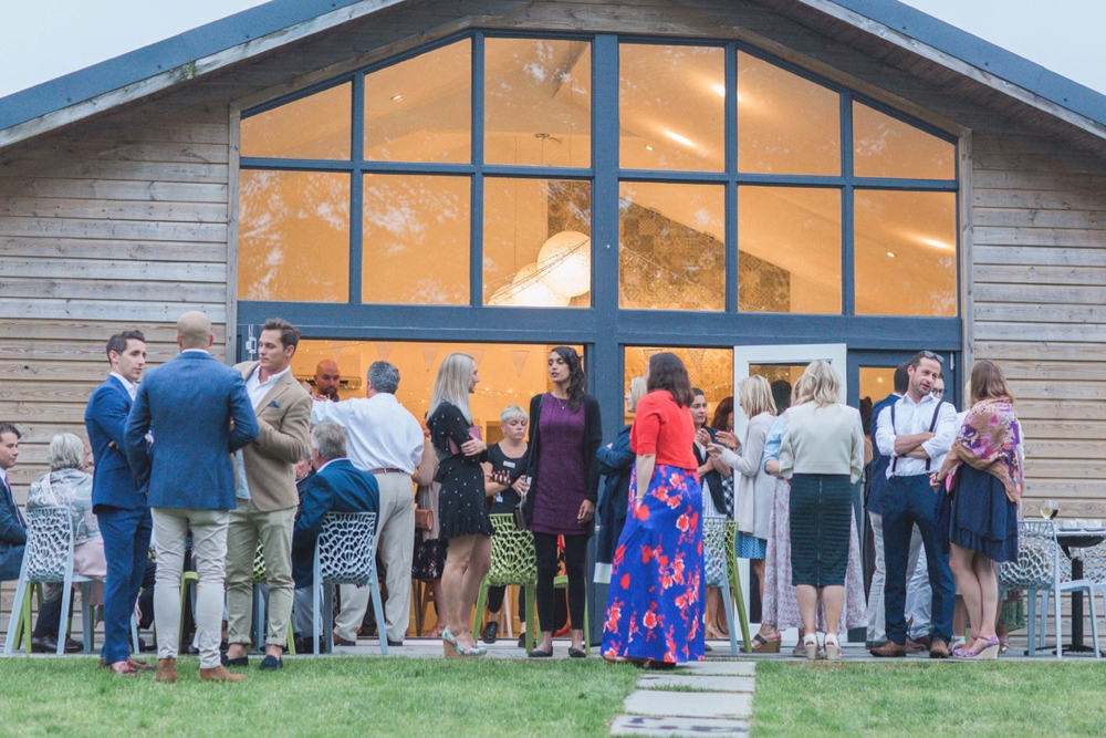This picture shows the Green Room Bar from the outside with the building filling the full shot. The lights are on inside and it is dusk. The doors are open and guests are selling onto the lawn and patio in front. The building is an a fram with a central glazed panel. The rest is clad in oak.