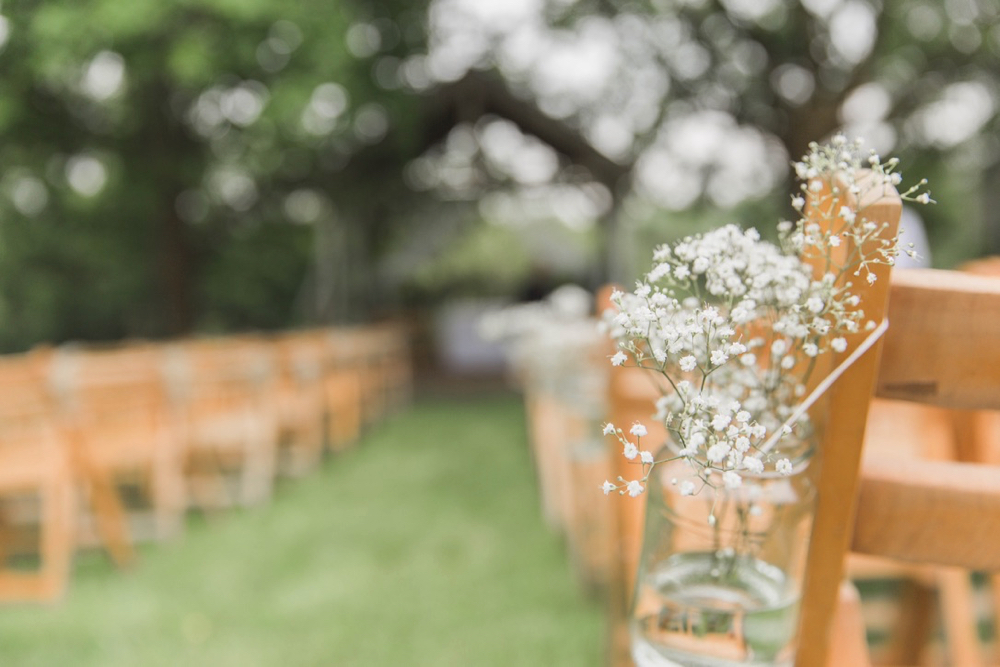 An image of the Oak Arbour set up for the ceremony. You can see the arbour and the 2 columns of rows of chairs.  In the foreground there is a jam jar strung with  twine  it is filled with gyp and is being used as a pew end.