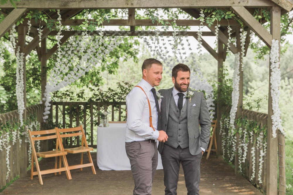 This is a picture of the bride and best man under the arbour waiting for the bride to arrive. The registrars table and 2 folding wooden chairs can be seen in the background.  The groom is on the righ. and is wearing a light grey suit. He has dark hair and a beard. The best man is dressed similarly but is not wearing a jacket or waistcoat. He has red braces. They are both looking towards where the bride will come from.