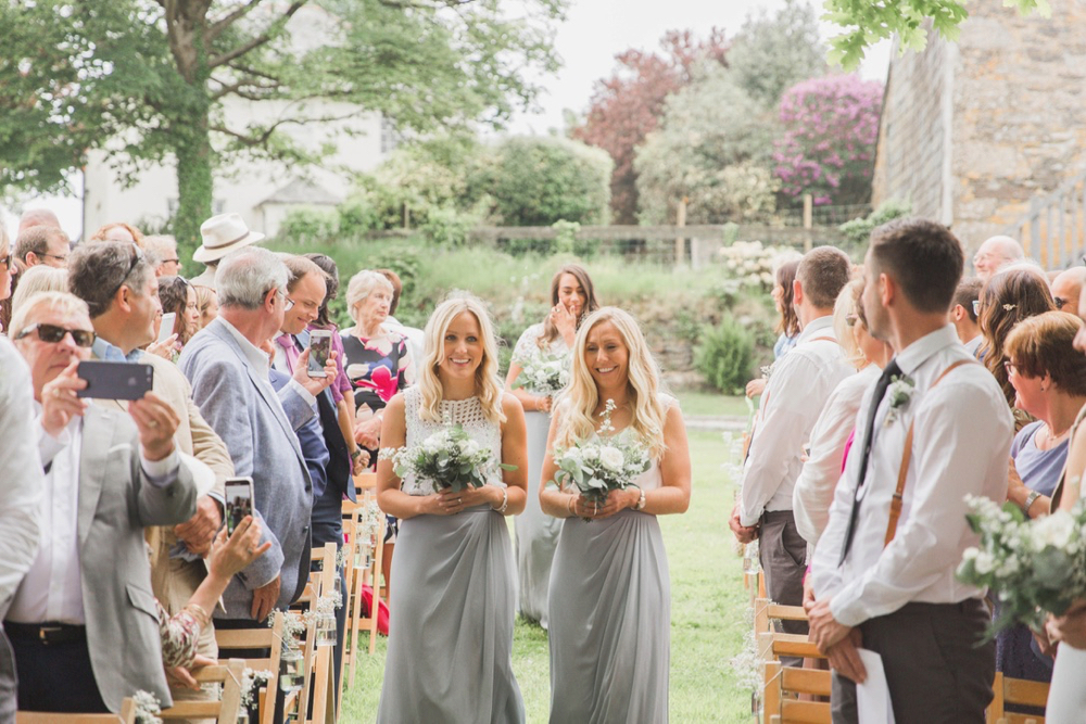 """This is a picture of two of the bridesmaids walking down the \""""aisle\"""" towards the arbour. They both have blond his that they are wearing loose. The hold bouquets in front of them. They are wearing grey skirts and white blouses. You can see guests standing beside their chairs on either side of the aisle. There are trees and stone barns in the background."""