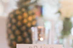 "A close up shot showing the detail of the table decor. There is a large  pineapple in the background sitting on a log slice. The table linen is white and there is a table place name set in a wooden holder. The sign says ""BRIDE\""."