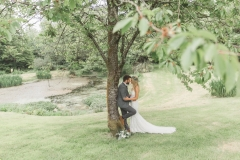 This is a picture of the bride and groom standing under a cherry tree by the lake.  About two thirds of the tree is shown and the couple look quite small next to it.  The couple are facing each other and kissing. The bride is on the right. She is  wearing a white, fitted, sleeveless dress with shoestring straps. She has blond hair that she is wearing loose. She is wearing  a flower garland and a veil. The groom is wearing a light grey suit. He has dark hair and a beard