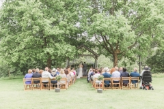 The Oak Arbour in May with each tree in full leaf. A full length shot showing the arbour set between 2 large oak tress. Wooden chairs are set out in the grass in frot of the arbour and the trees are in full leaf. Guests are seated in the chairs and the bride and groom are under the arbour.