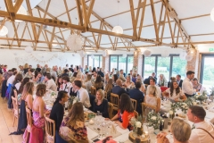 This is an image of the Red Brick Barn set up with long trestle tables. The centrepieces are pineapples on log slices. You can see the bar on the left hand side and the rustic beams in the ceiling. Guests are seated at the tables on wooden Cheltenham chairs
