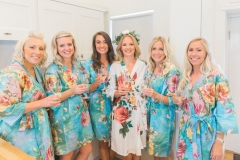 This is a picture of the bride and her 4 bridesmaids getting ready. They are standing in a row and wearing matching floral knee length gowns. The bridesmaids gowns are turquoise and the bride\'s is white. The bride is wearing a floral crown