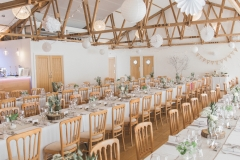 This is an image of the Red Brick Barn set up with long trestle tables. The centrepieces are pineapples on log slices. You can see the bar on the left hand side and the rustic beams in the ceiling.