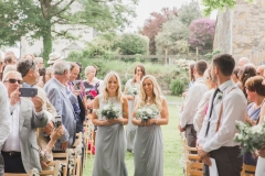 "This is a picture of two of the bridesmaids walking down the ""aisle\"" towards the arbour. They both have blond his that they are wearing loose. The hold bouquets in front of them. They are wearing grey skirts and white blouses. You can see guests standing beside their chairs on either side of the aisle. There are trees and stone barns in the background."