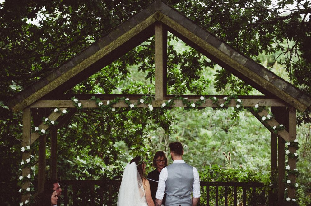 This is taken during an outdoor ceremony under the Oak Arbour. It is summer and the trees ae in ful leaf. The bride is on the left and the groom on the right.  The image is taken from the waist up with the Oak Arbour framing the shot.