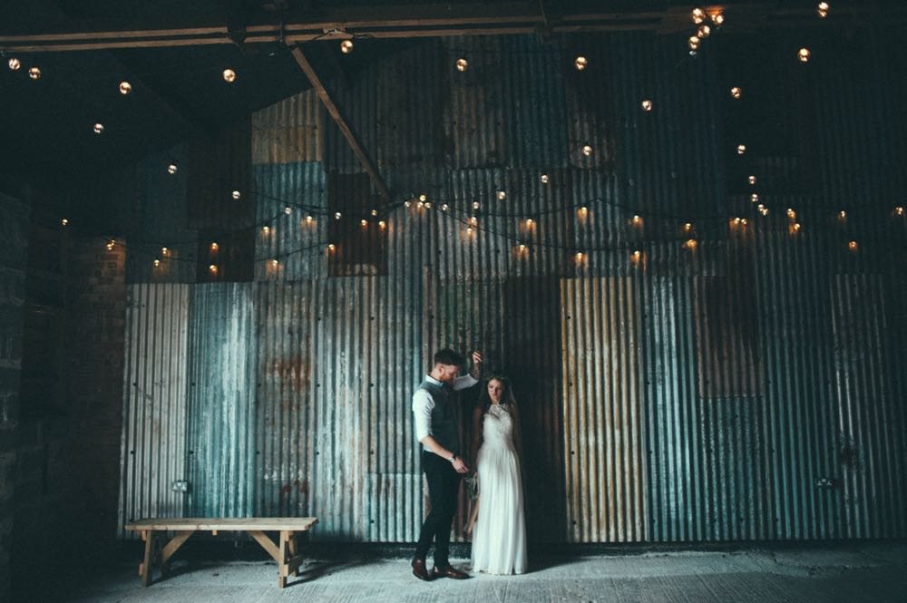 An imageof the couple taken in the Really Rustic Barn. The couple are standing and the bride is on the left and the groom on left. There are strings of festoon lighting above them