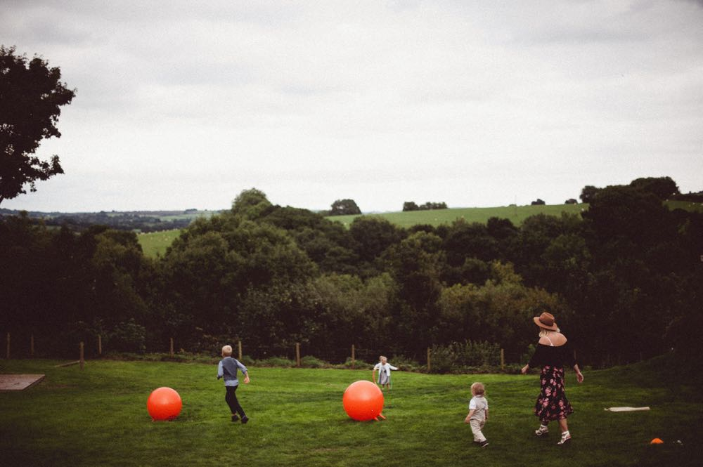 This shot shows some guests on the lawn with orange spacehoppers. There is a wood covered hill in the background.