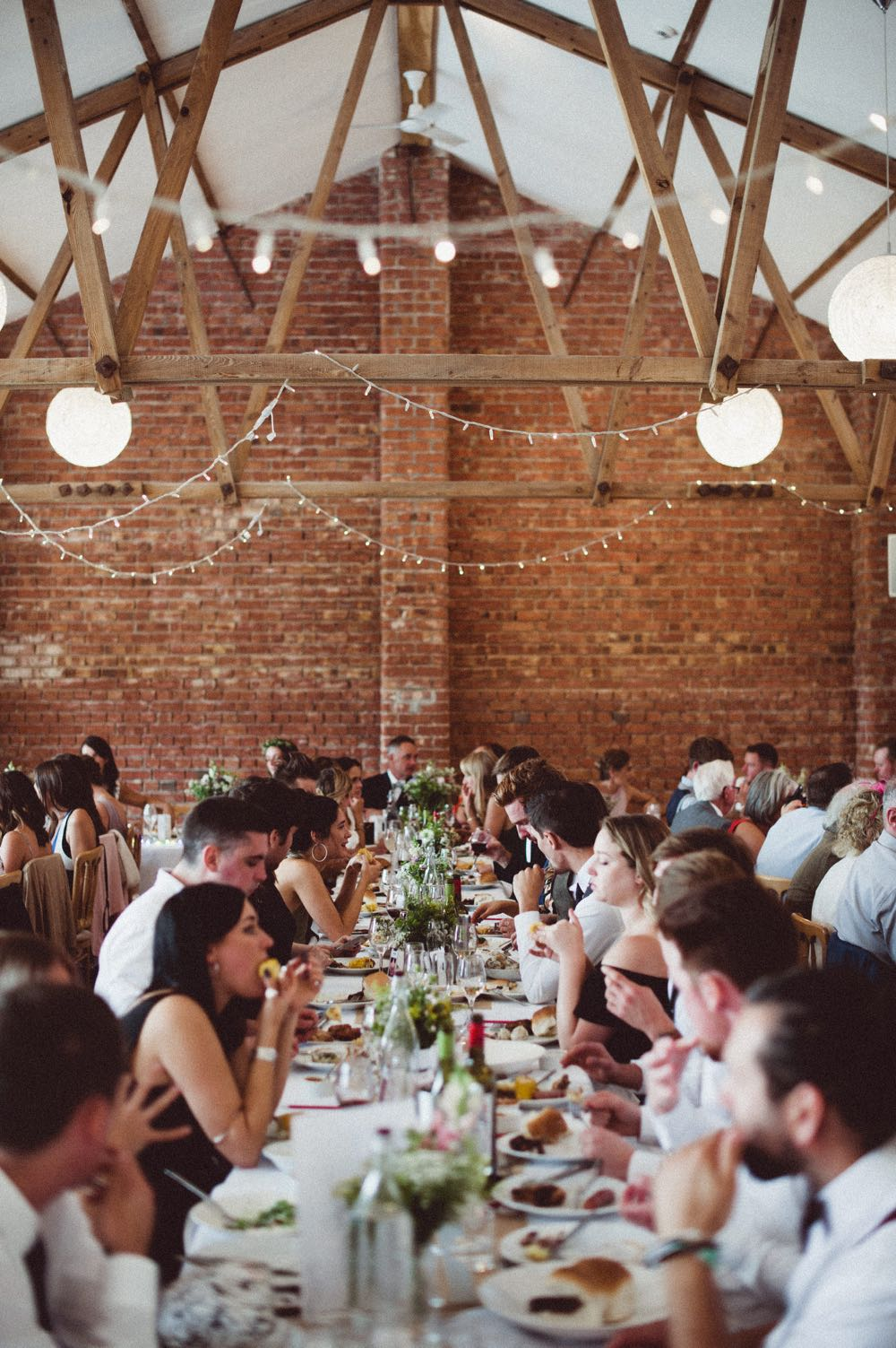 A group of guests are sitting at  trestle table in front of a Red Brick wall.