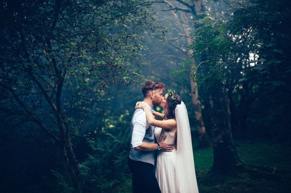 The couple are embacing in the woods. The light is dark and they are in a pool of light. The bride is on the right and the grrom on the left.