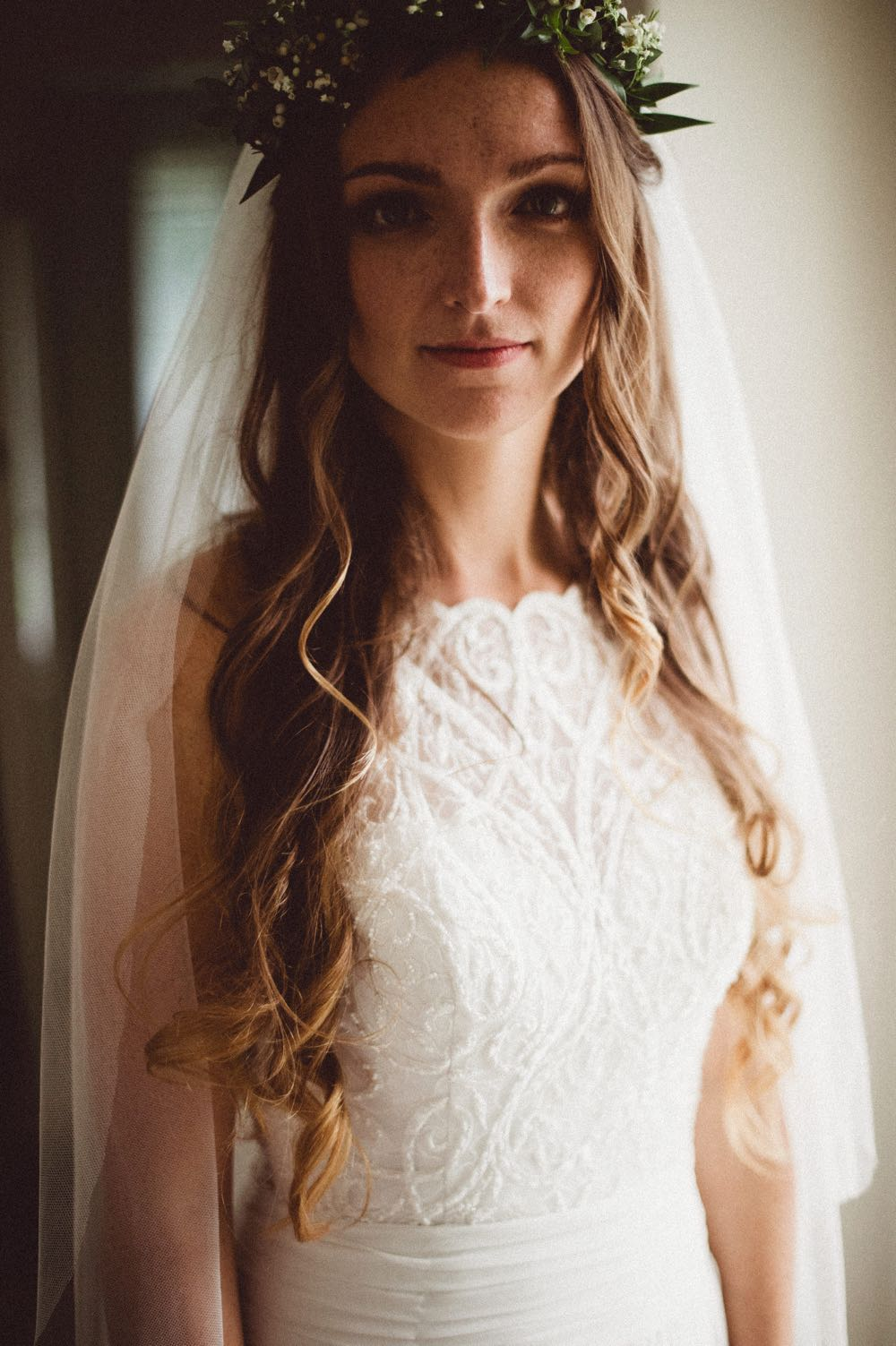 Thia is a close up, head and shoulders shot of the beautiful bride. She is wearing a a white sleeveless dress with lace details. She has long dark hair that she is wearing loose. She is smiling and looking at the camera.