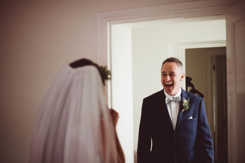 This picture shows the bride\'s father seeing her in her wedding dress for the first time. They are both shown from the waist up. You can see the back of the brde and you can see the faceof thefather of the bride. He is open-mouthed and very happy. The bride wears a veil. The fatherof the bride weara a navy suit, white shirt and bowtie