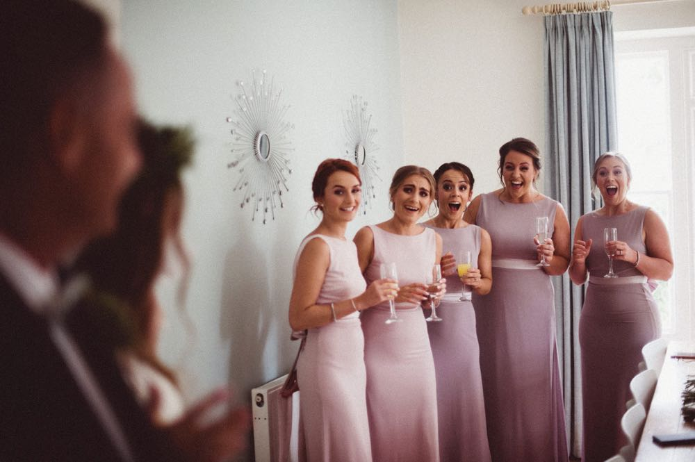 This image shows the 5 bridesmaids seeing the bride in her derss for the first time. The bride and her father are in the far left of the shot shown from the side. The image is focussed on the breidesmaids. The are facing the camera, wearing pink, sleeveless, full-length gowns. They are holding chanpagne  glassses. Their faces are full of joy.