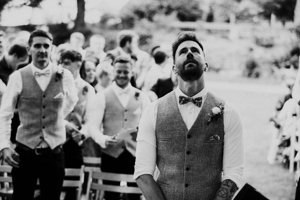 This image has the groom in the middle. He is waiting at the Oak Arbour with his back to the the guests. He is wearing a white shirt, a bowtie and a tweed waistcoat. This is a black and white shot. You can see 2 of his groomsmen behind him and they are similarly dressed. The groom looks really nervous and is looking upwards.
